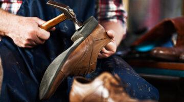 Schuhmacher mit Hammer und Schuh
