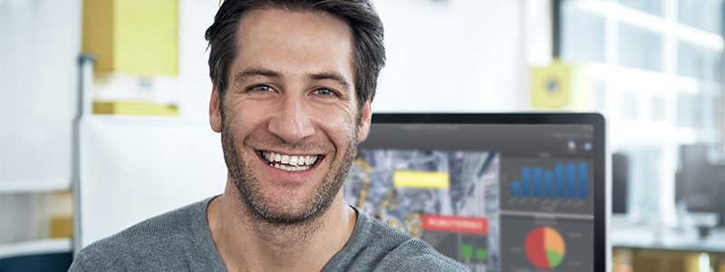 Ein lachender Mann vor einem Computer mit cronetwork MES