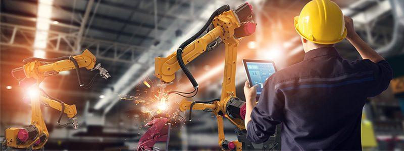 Ein Mann mit gelbem Helm und Tablet in der Hand schaut auf einen Roboterarm
