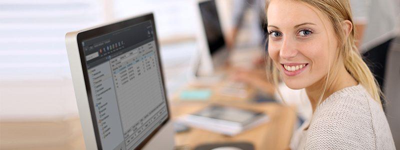 Eine blonde Frau benutzt cronetwork Personalzeit auf Ihrem PC