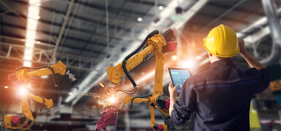 Ein Mann mit Helm und Tablet steht vor einem Roboterarm