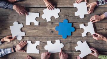 Mehrere Personen bauen ein großes Puzzle mit einem blauen Teil in der Mitte