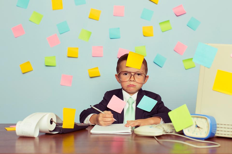 Ein Kind mit Brille und gelbem Post It auf der Stirn