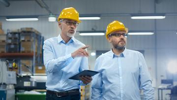 Zwei Männer mit gelbem Helm und Hemd
